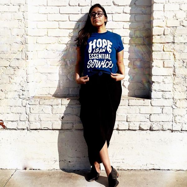 "Ra wearing a blue shirt and black skirt. Shirt says ""Hope is an Essential Service"". Links to her Etsy shop."
