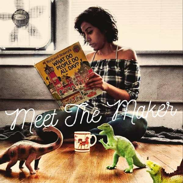"A picture of Ra Avis, holding a book by Richard Scarry called ""What do People Do all day?"".  She is sitting on the floor with toy dinosaurs around. Over the photo, it says ""Meet the Maker"""